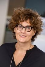 Anne Schilder, a white woman with black-framed glasses and short curly hair, smiles at the camera