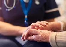 Image of an elderly person's hands being held by a health professional