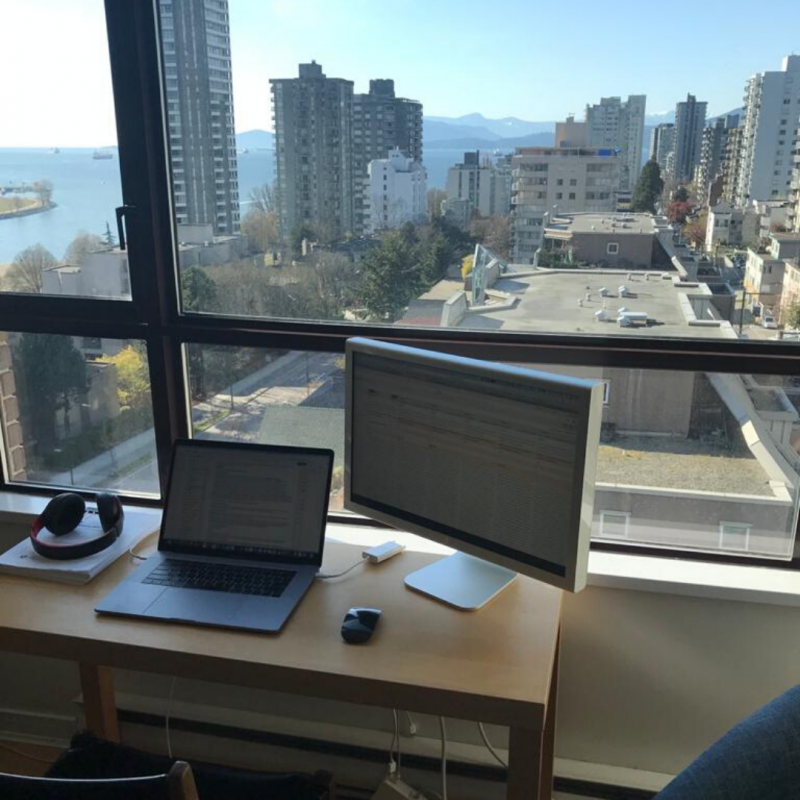 Picture of a computer desk against a window with ocean view