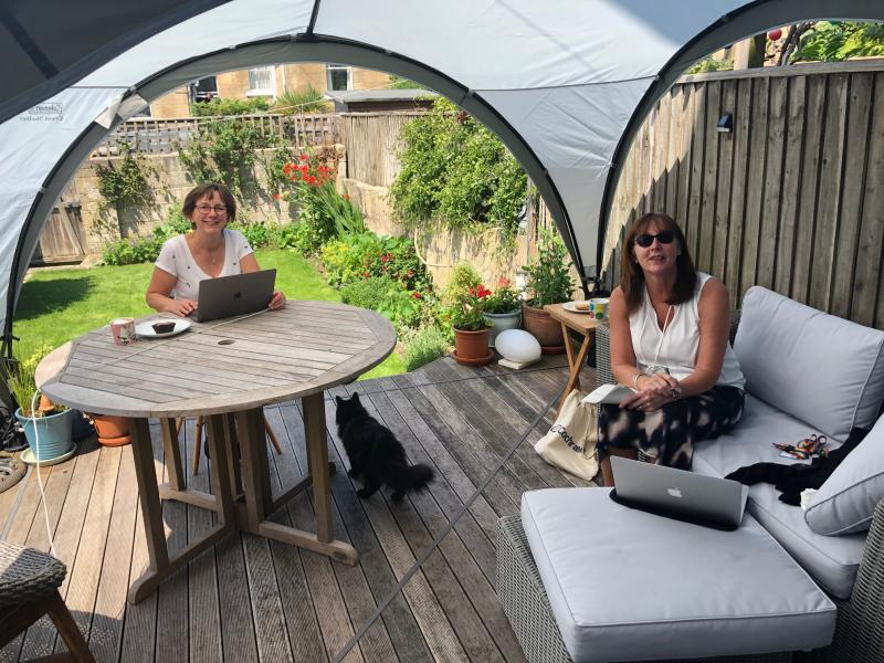 Two smiling women sit in a garden at a patio table
