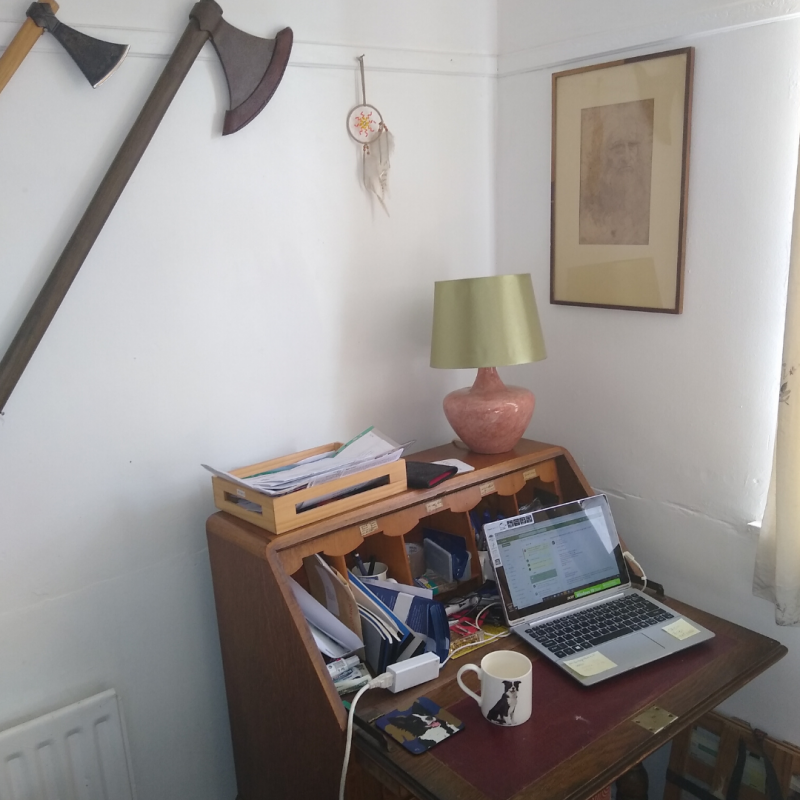 Picture of a desk with axes hanging over it